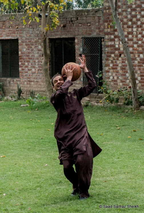 Ali plays a game of catch with his classmates on the lawns of the society.
